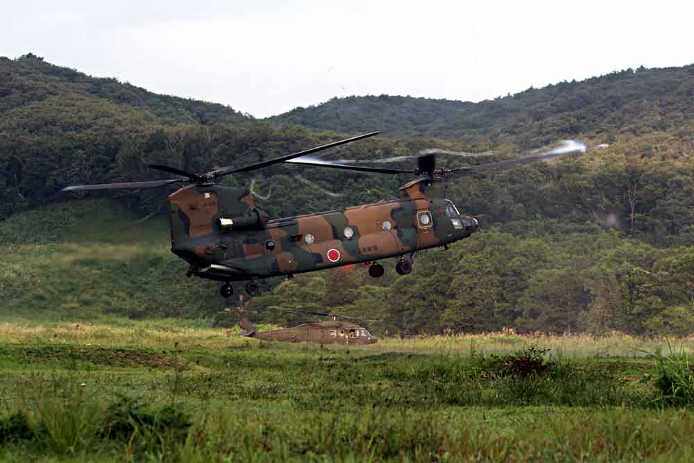 A Japanese CH-47 Chinook lands next to a U.S. Army UH-60 Black Hawk as part of a training assault event during Exercise Orient Shield 2018.
