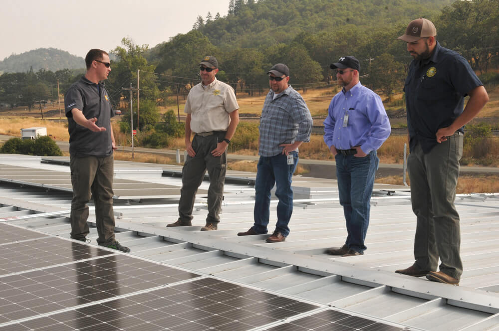 FROM LEFT: Robert Johnson, supervising electrician for Sunlight Solar, briefs James Odan, operations facilities specialist; Eric Manus, Oregon military department project manager; Mark Williams, Oregon military department project manager; and Steven Roche, operations facilities specialist on a then-newly installed photovoltaic solar panel system at the Roseburg Readiness Center, Ore. Oregon Army National Guard photo by SSG Anita VanderMolen