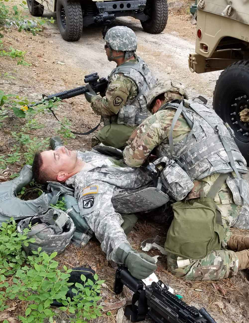 SSG Bryn Mandl conducts a mock medical evacuation on SFC Roberto Ramos, while PFC Alfonso Alicia provides cover as part of a training simulation during the 350th Financial Management Support Detachment's mobilization exercise.