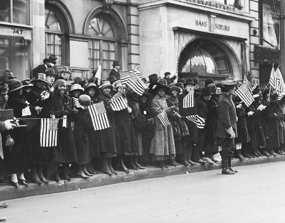 """Crowds in New York City await the parading Soldiers of the 369th """"Harlem Hellfighters"""" Infantry Regiment, New York Army National Guard, after the Soldiers returned home as heroes for victoriously serving as the first African American unit to serve as part of the U.S. expeditionary force in World War I. National Archives photo by Paul Thompson"""