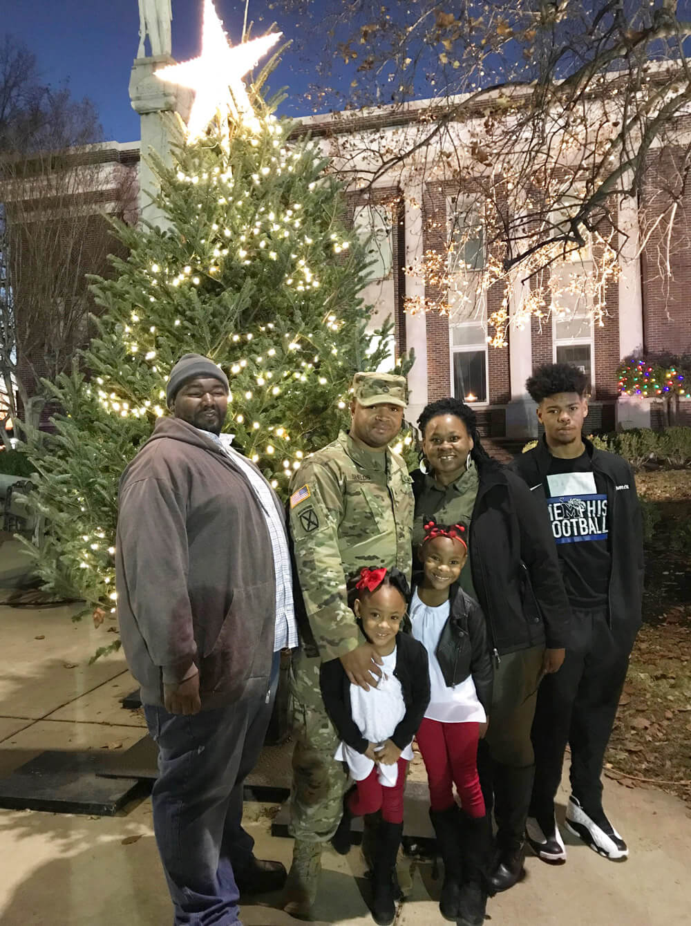 SSG Patrick Shields (second left) and his brother Gregory Shields (far left) stand with SSG Shields' wife and children before the brothers begin to lead as grand marshals in the 2018 Brownsville City Christmas Parade, an honor bestowed on the Shields brothers for their selfless acts at Haywood High School.