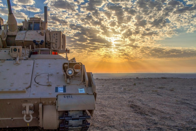 The sun rises above an M2A3 Bradley Infantry Fighting Vehicle at Al-Ghalail Range, Qatar, November 2018. The Mississippi Army National Guard Soldiers of the 2nd Battalion, 198th Armor Regiment, Task Force Spartan, spent the pre-dawn hours staging their Bradley in preparation for a combined arms live-fire drill held as part of Exercise Eastern Action 2019, a command post and field training exercise conducted in partnership by the U.S. Army and the Qatari Emiri Land Forces. Mississippi Army National Guard photo by SPC Jovi Prevot