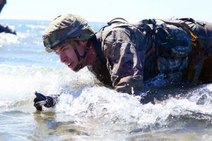 Oregon Army National Guard's SGT Dane Moorehead of the 82nd Brigade Troop Command, high-crawls to shore in full battle gear as part of the Omaha Beach event during the 2017 Oregon Best Warrior Competition at Camp Rilea, Ore. Oregon Army National Guard photo by SFC April Davis