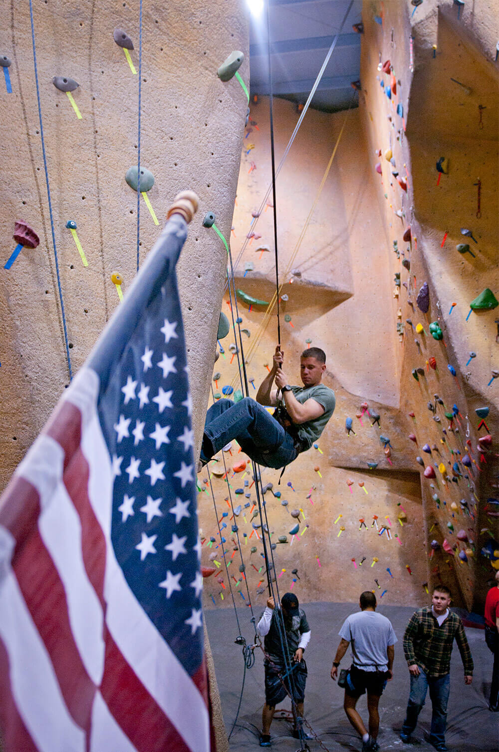 1LT Nick Westendorf, an operations officer with Headquarters and Headquarters Company, 8th Engineer Battalion, belays down after climbing a wall in the Boulders Sport Climbing Center in Harker Heights, Texas, as part of a Warrior Adventure Quest event.