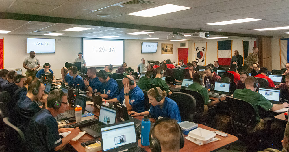 A joint group of U.S. service member teams from the Army, Air Force and Navy listen, decipher and translate in-field audio during the Operational Skills Test portion of the 2019 Polyglot Games as part of the 300th Military Intelligence Brigade's 30th Annual Language Conference. National Guard Bureau photo by Luke Sohl