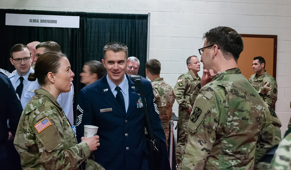 Left to Right: SSG Rose Bowman, 142nd Military Intelligence Battalion, Utah Army National Guard; SMSgt Jacob Hall, 169th Intelligence Squadron, Utah Air National Guard; and SSG Thomas Good, 142nd Military Intelligence Battalion, Utah Army National Guard, mingle during the expo portion of the 300th Military Intelligence Brigade's 30th Annual Language Conference. National Guard Bureau photo by Luke Sohl