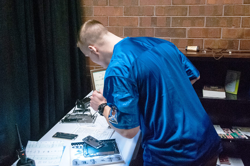 SPC Michael Renner of the 341st Military Intelligence Battalion, Washington Army National Guard, uses personal items of a fictional adversary to create a mock profile during the Site Exploration event of the 2019 Polyglot Games at the brigade's 30th Annual Language Conference, March 2019. National Guard Bureau photo by Luke Sohl