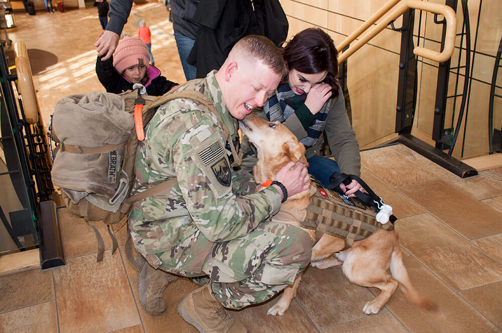SSG Nicholas Milbrath of North Dakota's 191st Military Police Company is greeted by a four-legged friend upon returning from a yearlong mission in Kabul, Afghanistan. North Dakota Army National Guard photo by SSG Eric W. Jensen
