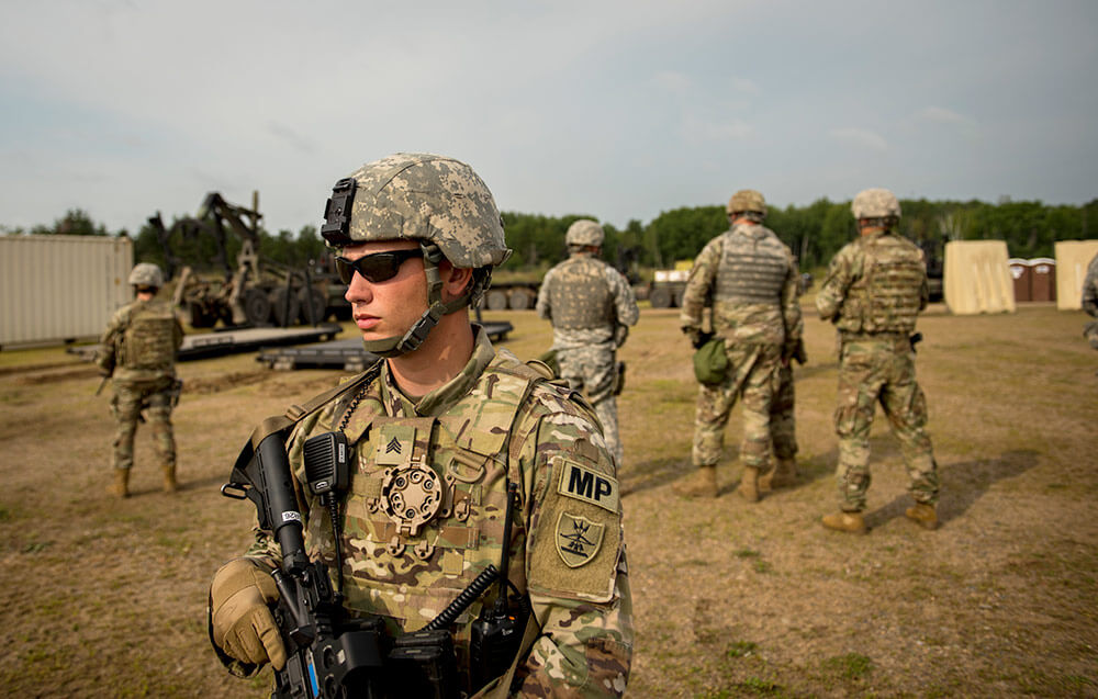 Soldiers with the 191st Military Police Company form a perimeter around 347th Regional Support Group Commander COL Lowell Kruse during a personal security detail at Camp Ripley August 2017 as part of the unit's combat support pre-deployment training exercise. North Dakota Army National Guard photo by SSG Patrick Loch