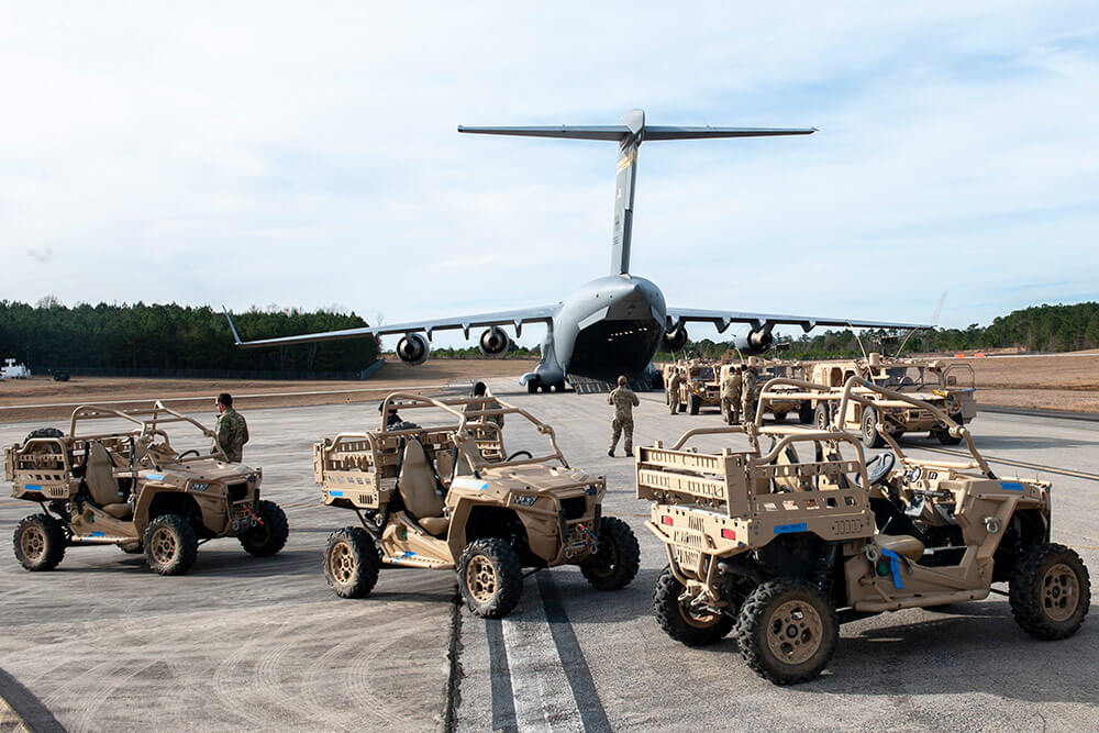 Soldiers and vehicles from the 3rd Special Forces Group prepare to board a Hawaii Air National Guard C-17 Globemaster January 2019 for transport to the Gulfport Combat Readiness Training Center, Miss., during exercise Southern Strike. Hawaii National Guard photo by SrA John Linzmeier