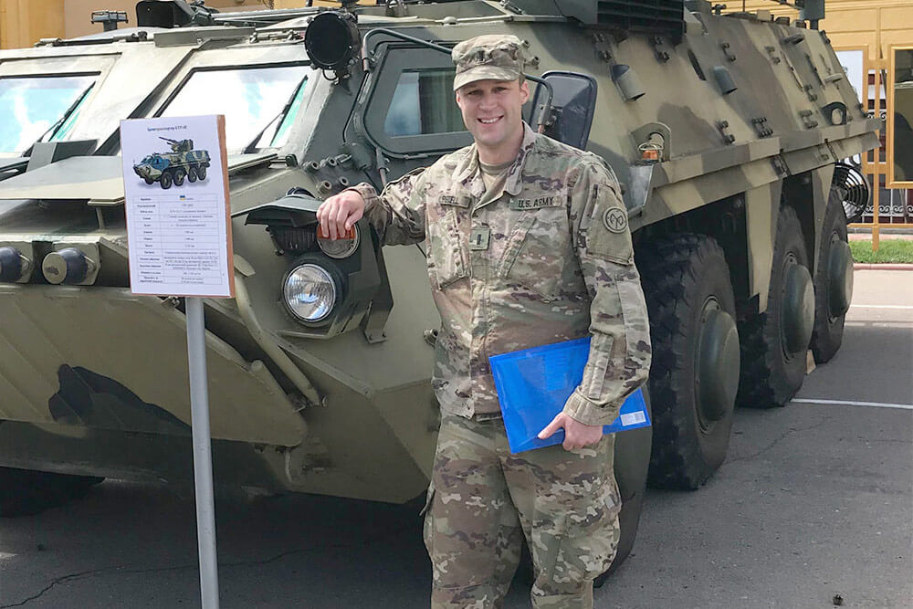 New York Army National Guard's 1LT James Pistell, executive officer of Headquarters and Headquarters Troop 2nd Battalion, 101st Cavalry, poses by a Ukrainian personnel carrier at the Yavoriv Combat Training Center near Livov, Ukraine. Photo courtesy 1LT James Pistell