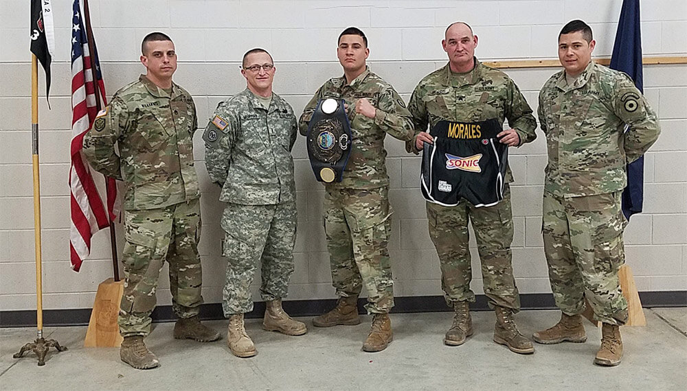 SPC Efrain Morales (center) displays his Championship Belt alongside fellow members of 731st Transportation Company —left to right: SSG Williams, WO Murphy, SGT Morris and SGT Macias. Photo courtesy SPC Efrain Morales