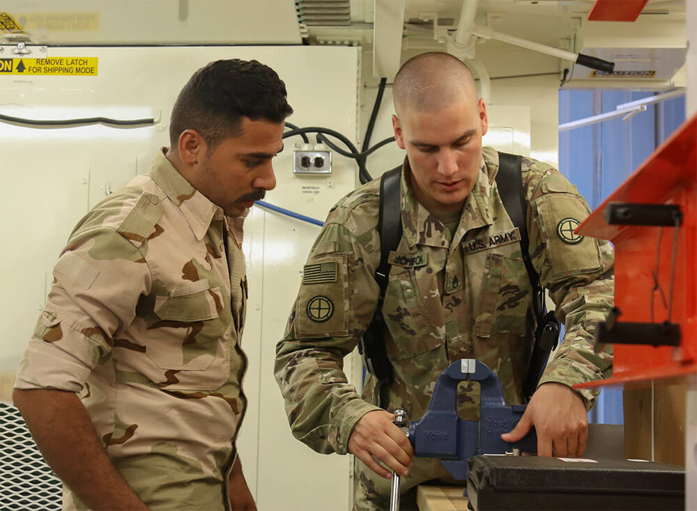 SSG David Johnson, the powertrain shop chief assigned to B Company, 935th Aviation Support Battalion, Illinois Army National Guard, explains to Iraqi aviation engineers how to set up the electrical outlets inside a portable maintenance shop container on the Camp Taji Military Complex, October 2018. Missouri Army National Guard photo by SGT Emily Finn