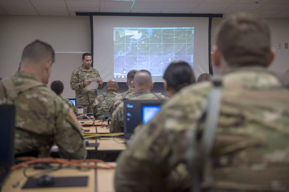 SGT Lawrence Bass, convoy commander with Headquarters Company, 271st Brigade Support Battalion, 45th Field Artillery Brigade, briefs his unit during training on the Virtual Battle Space III (VBS3) system, April 2019, in preparation for team exercises in virtual scenarios that will be held as part of an upcoming Exportable Combat Training Capability—Operation Western Strike. Oklahoma Army National Guard photo by CPT Leanna Maschino