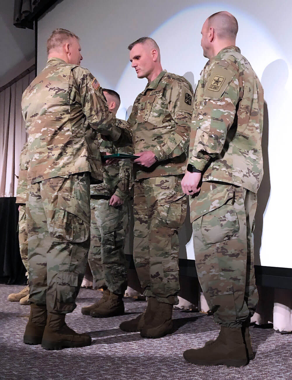 SSG Sergi Corduneanu, a crypto-linguist with Delta Company, 341st Military Intelligence Battalion, 300th Military Intelligence Brigade, Washington Army National Guard, is awarded a plaque during the brigade's annual language conference where he was selected as the 300th's language professional of the year. Photo courtesy Washington National Guard