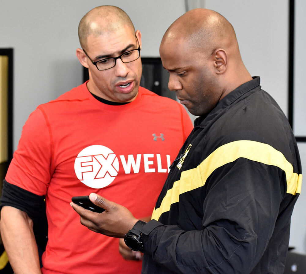 2LT Delvon Anderson assigned to the 629th Military Intelligence Battalion receives instruction from Chad Ayinde, FX Well director, on how to use a fitness app as part of FX Well's Fit Well training program in which the battalion is participating in preparation for the new Army Combat Fitness Test. Maryland Army National Guard photo by MAJ Kurt Rauschenberg