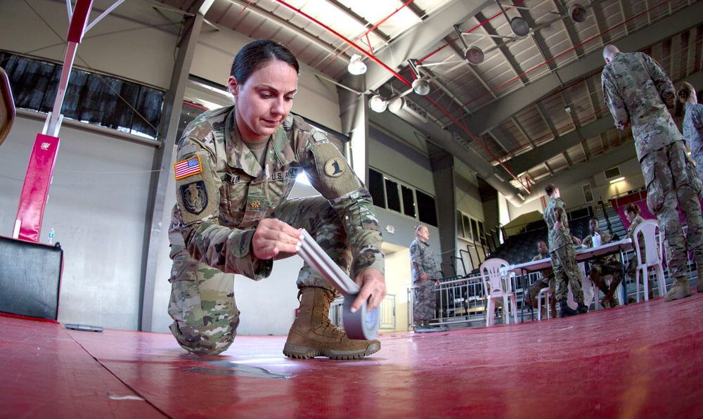 MAJ Alexandra Dillion, a nurse corps officer with the Delaware Army National Guard Medical Detachment, creates directional arrows with strips of duct tape in preparation for a joint Innovative Readiness Training in Ponce, Puerto Rico, April 2019. U.S. Marine Corps photo by Sgt Andy O. Martinez