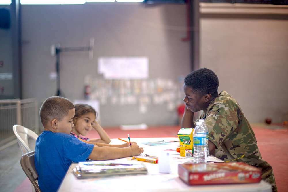 Children play Tic-Tac-Toe with PFC Kwabena A. Anim-Appiah, a combat medic with Delaware Army National Guard Medical Detachment, during a joint Innovative Readiness Training held at Ponce, Puerto Rico, May 2019. U.S. Marine Corps photo by Sgt Andy O. Martinez