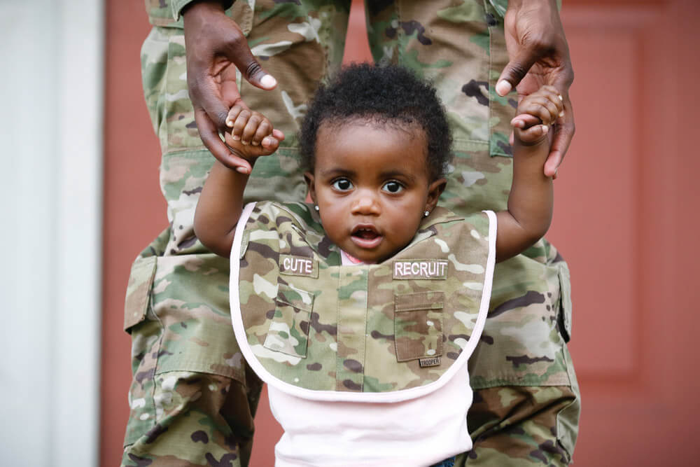 Amore Cox stands with the help of her mother, SPC ShaTyra Reed, a public affairs mass communications specialist with the 22nd Mobile Public Affairs Detachment, XVIII Airborne Corps Headquarters and Headquarters Battalion, in Fayetteville, N.C. U.S. Army photo by PFC Hubert D. Delany III
