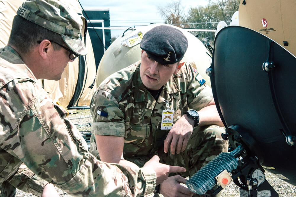 British Armed Forces soldier, Corp. Michael Beasley-Wood from the 37th Royal Signals Regiment 4-8 Signal Squadron, takes direction from CPL Jack Rodriguez of the 46th Military Police Command in learning about the communication systems used during the Vibrant Response 2019, May 2019. Michigan Army National Guard photo by SPC Aaron Good