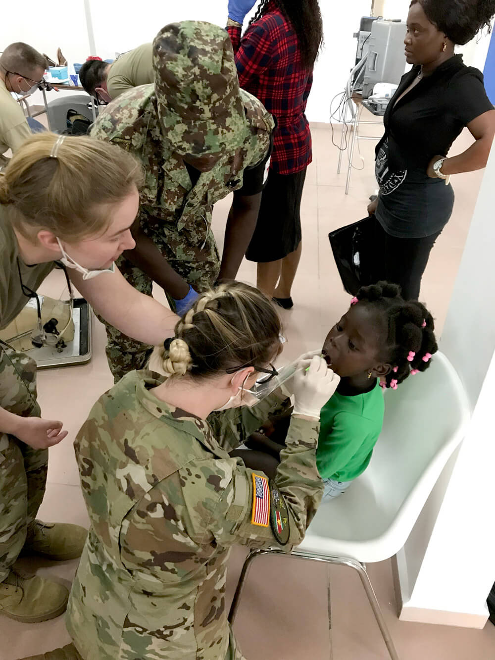 South Dakota Army National Guard's SPC Kirstin Gortmaker paints fluoride varnish on a young girl's teeth as part of a humanitarian services deployment to South Dakota's State Partner, Suriname, April 2019. South Dakota Army National Guard photo by SSG Samantha Wempe