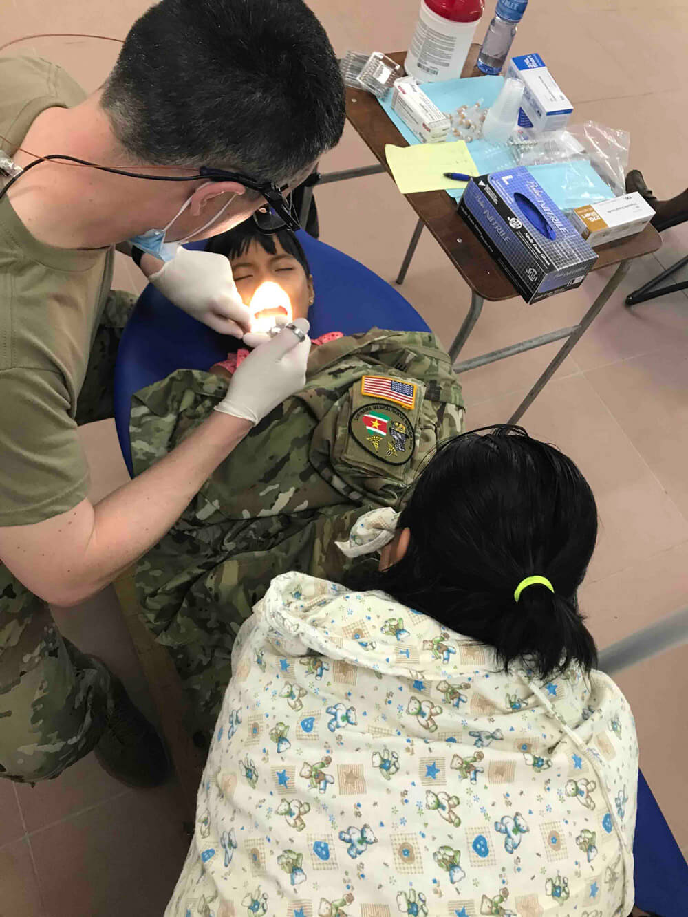 MAJ Kevin Donlin, a dentist with the South Dakota National Guard, performs a tooth extraction on a young girl as her mother watches in Albina, Suriname, April 2019. South Dakota Army National Guard photos by LTC Anthony Deiss