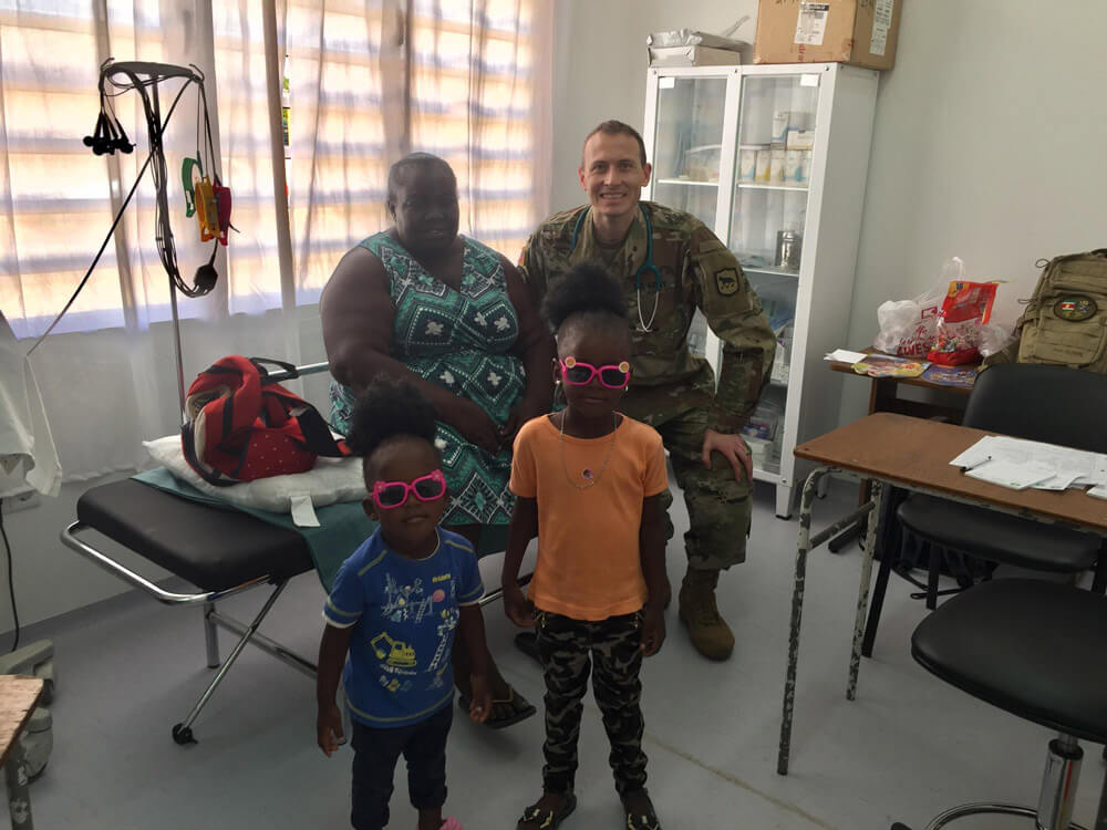 MAJ Ronovan Ottenbacher, a field surgeon and physician with the South Dakota National Guard, poses with a Surinamese woman and her children as they prepare to receive a medical examination in Albina, Suriname, April 2019. South Dakota Army National Guard photos by LTC Anthony Deiss