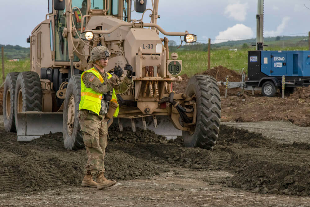 CPT Edwin Higginbotham of 297th Regional Support Group, Alaska Army National Guard, guides a dump truck onto a work site during exercise Resolute Castle in Cincu, Romania, May 2019. Alaska Army National Guard photo by PVT Grace Nechanicky