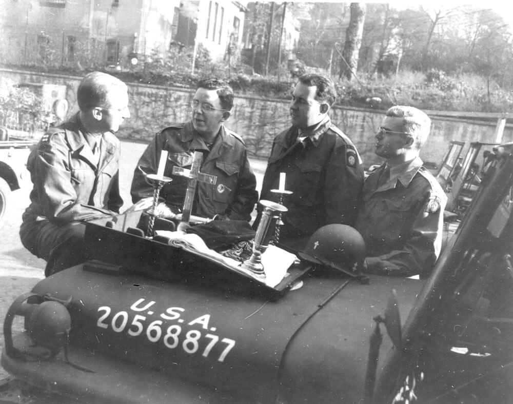 Unidentified chaplains hold an impromptu service atop their Army Jeep while visiting Soldiers of the 82nd Airborne Division during WWII. Public domain photo