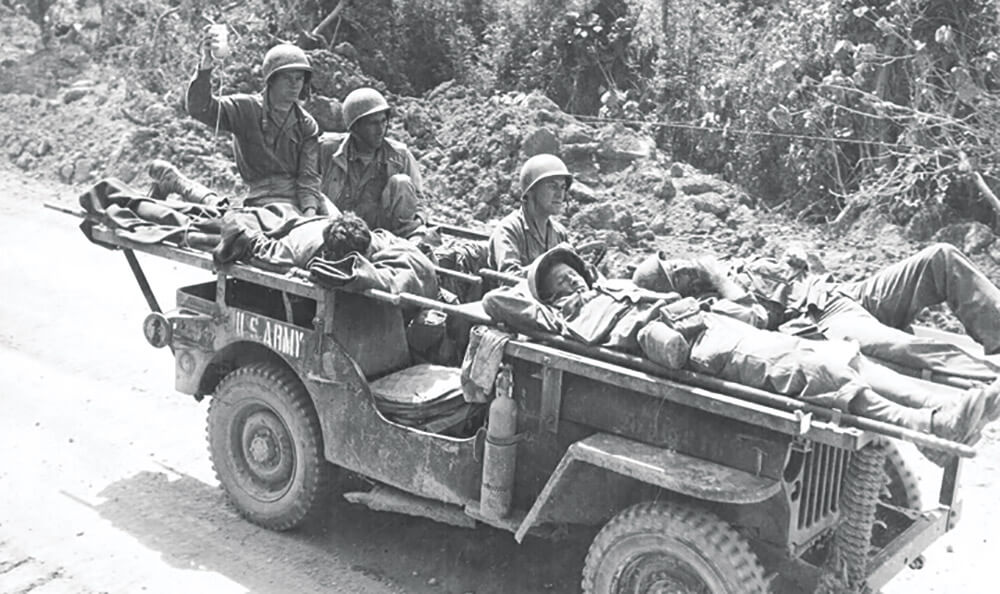 Soldiers of the 102nd Medical Battalion evacuate four wounded U.S. Soldiers to a rear area field hospital on an ambulance jeep in Okinawa, April 22, 1945. Photo courtesy Otis Historical Archives, National Museum of Health and Medicine