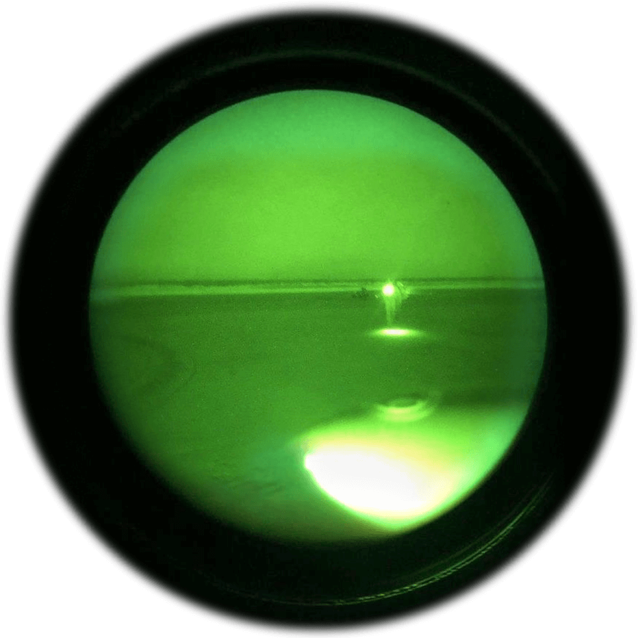 Seen through night vision goggles, Alaska Army National Guard UH-60 Black Hawk crew chief, SPC Jeff Hartmann approaches a hunting party gathered by their campfire on a small island sandbar on the Yukon River in Alaska, May 2019. Photo courtesy Alaska Army National Guard