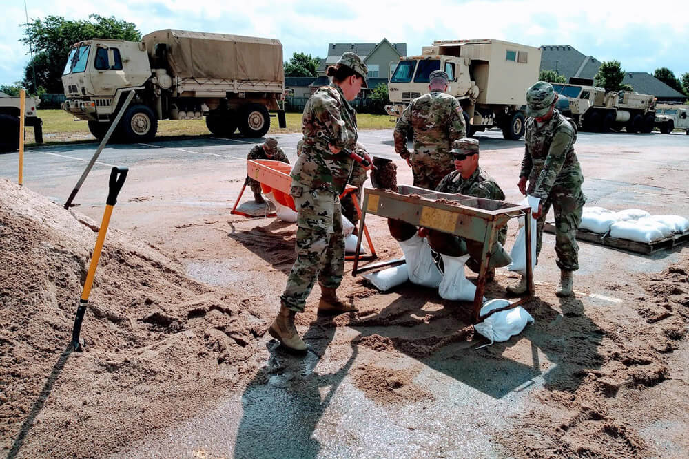 SPC Jessica Post (left), a member of the 120th Medical Company, Oklahoma Army National Guard, shovels sand into a manual sandbag filler with the aid of fellow Soldiers in Bixby, Okla., during flood relief efforts, May 2019. Oklahoma Army National Guard photo by SPC Jessica Todd