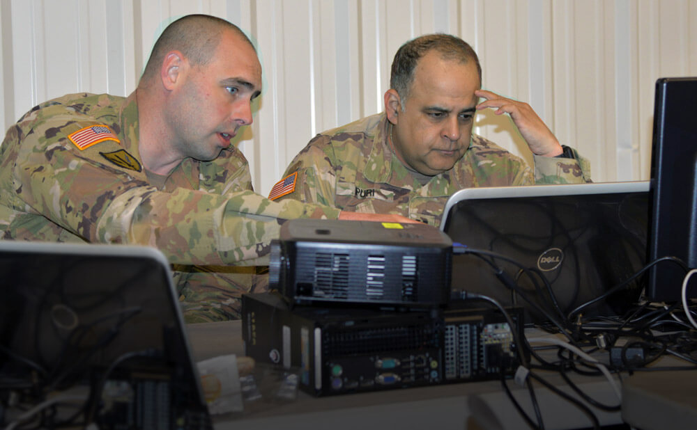 CW2 Brian Gosch (left) and CPT Sameer Puri, both members of the Washington National Guard's Cyber Mission Assurance Team, work to identify network abnormalities during the Cyber Shield 19 training exercise held at Camp Atterbury, Ind., April 2019. Washington National Guard photo by Bradford Leighton