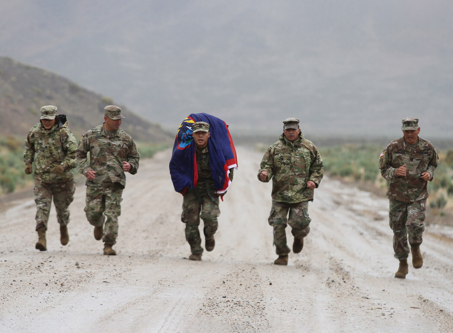 SGT Jermain Mendiola, center, of the Guam Army National Guard, enters the finish line of a grueling 12-mile ruck march May 23 in Hawthorne, Nev., during the 2019 Army National Guard Region 7 Best Warrior Competition (BWC). SGT Mendiola is flanked by CSM Agnes Diaz, Guam National Guard senior enlisted advisor; SGM Bruce Meno; SSG Dino Cruz; and CSM Ron Brantley. The winner advances to the National Guard BWC later this year. California Army National Guard photo by SSG Eddie Siguenza